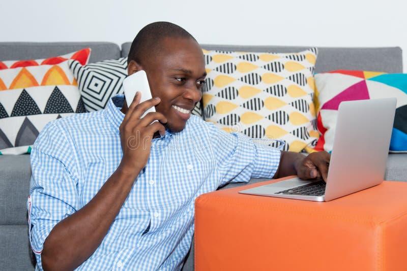 有计算机和手机的英俊的非裔美国人的人 库存照片
