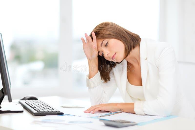有计算机和纸的疲乏的女实业家 免版税图库摄影