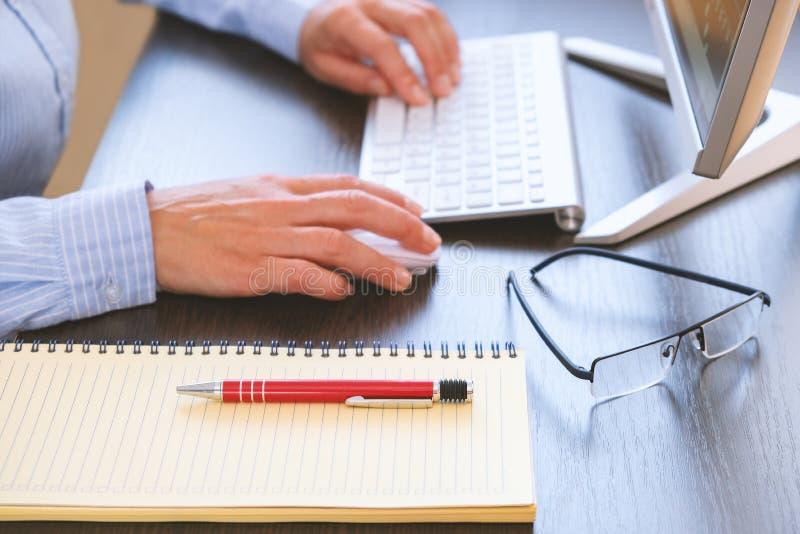 有计算机和键盘的办公桌在背景中 笔记本和笔为工作纪录准备 免版税库存照片