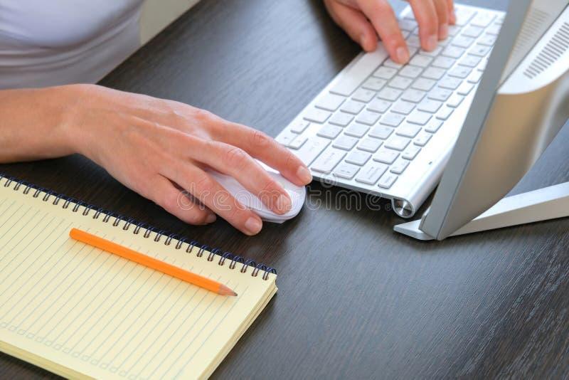 有计算机和键盘的办公桌在背景中 笔记本和笔为工作纪录准备 库存图片