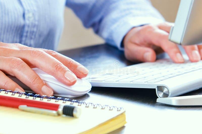 有计算机和键盘的办公桌在背景中 笔记本和笔为工作纪录准备 免版税库存图片