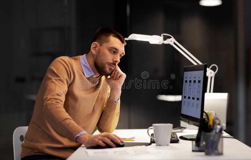 有计算机工作的网设计师在夜办公室 库存图片