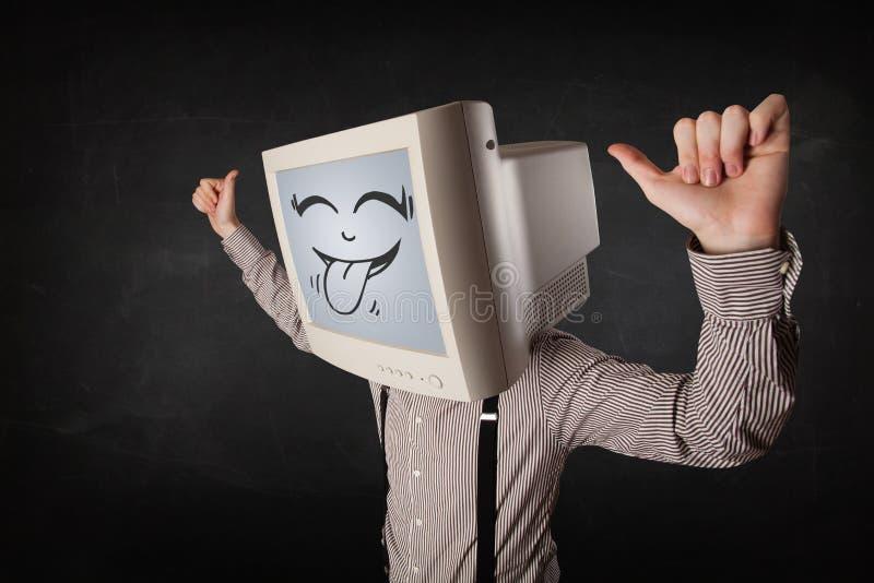 有计算机显示器和一张兴高采烈的面孔的愉快的商人 图库摄影