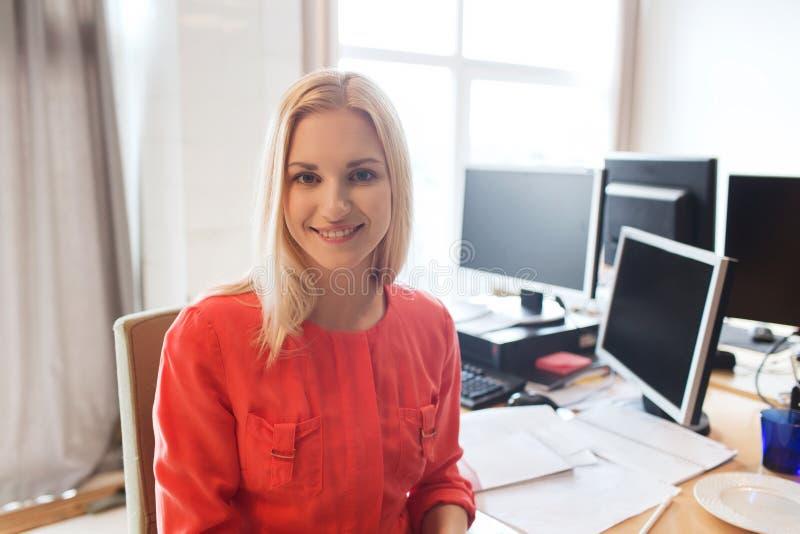 有计算机的愉快的创造性的女性办公室工作者 免版税库存图片
