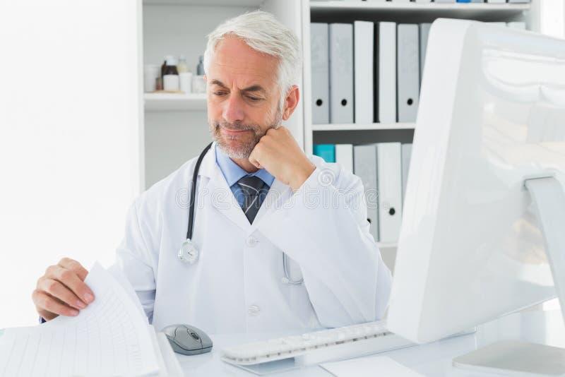 有计算机的成熟男性医生在医疗办公室 图库摄影