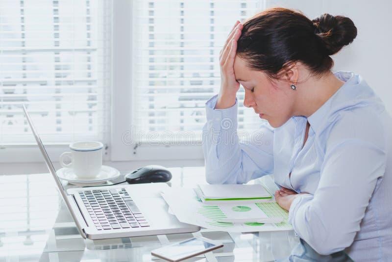 有计算机的疲乏的女商人在办公室、重音和问题 免版税图库摄影