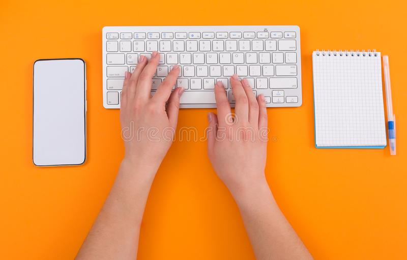 有计算机的,手,在橙色背景的办公用品办公室工作场所 ?? 顶视图概念 免版税库存图片