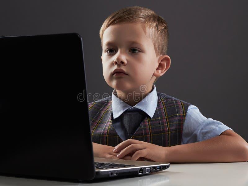 有计算机的年轻男孩 看在笔记本的滑稽的孩子 免版税库存图片