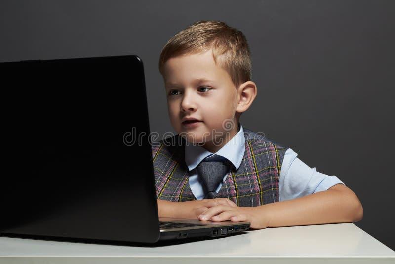 有计算机的年轻男孩 看在笔记本的滑稽的孩子 免版税库存照片