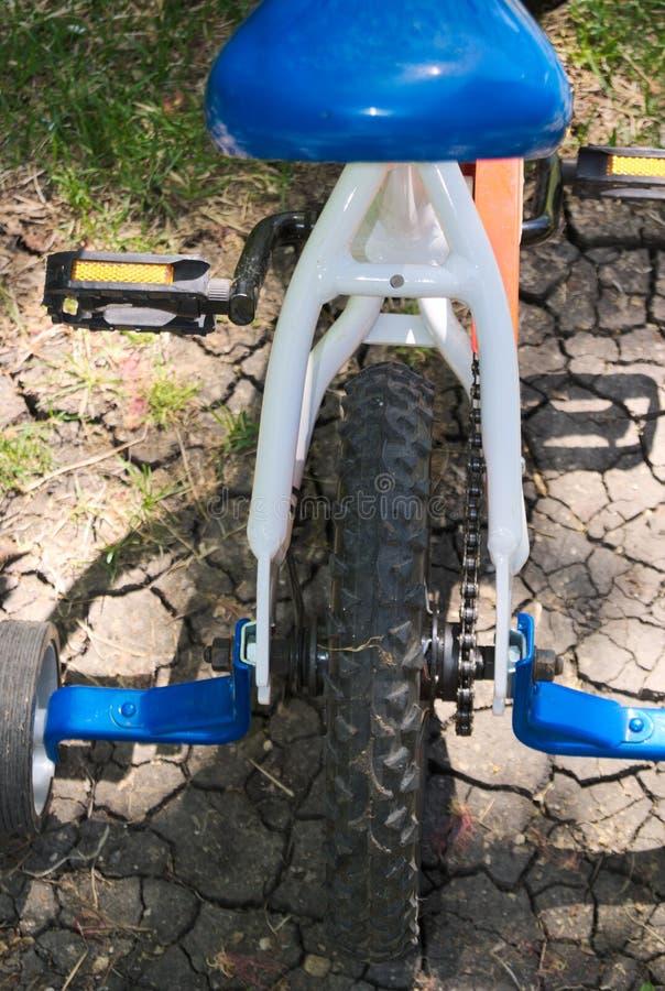 有训练轮子的儿童的自行车从后面孩子轮胎自行车 库存照片