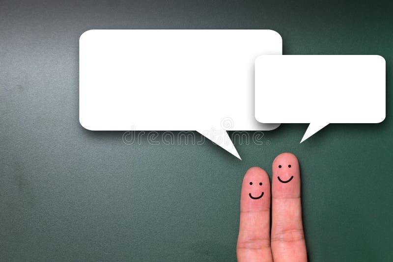 有讲话泡影的两个微笑的手指 库存照片