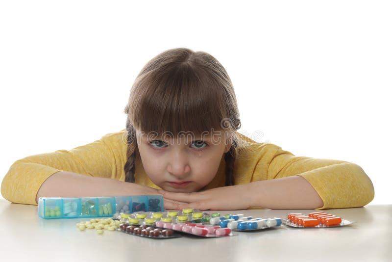 有许多不同的药片的哭泣的小孩在白色 药剂醉的危险 库存照片