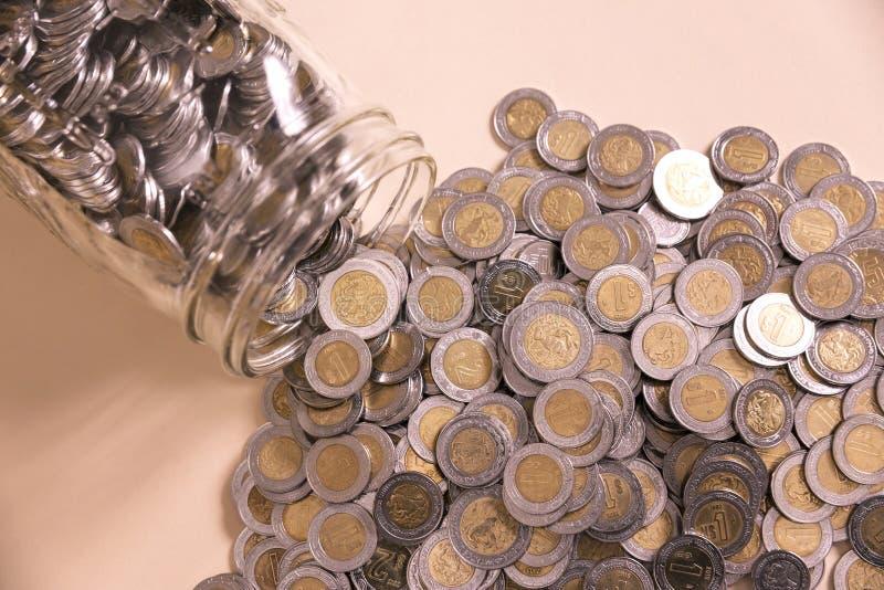 有许多墨西哥比索的玻璃瓶子 免版税库存照片