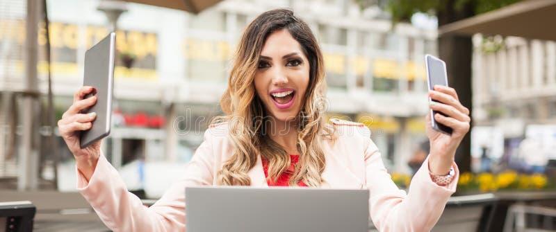 有许多屏幕、mobils、片剂和膝上型计算机的歇斯底里的妇女 免版税库存图片
