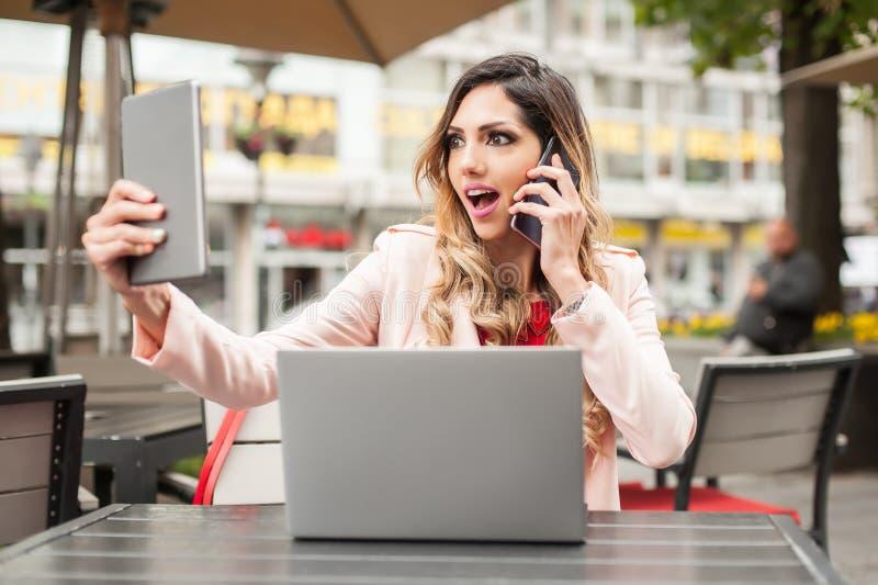 有许多屏幕、mobils、片剂和膝上型计算机的歇斯底里的妇女 库存图片