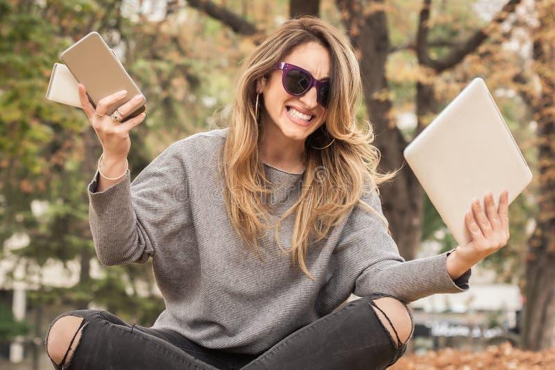 有许多屏幕、mobils、片剂和lapto的歇斯底里的女孩 免版税图库摄影