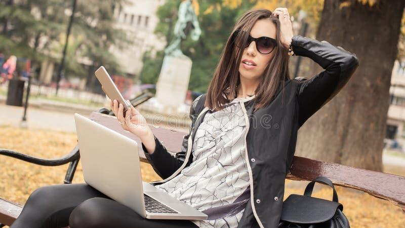 有许多屏幕、mobils、片剂和lapto的歇斯底里的女孩 免版税库存照片