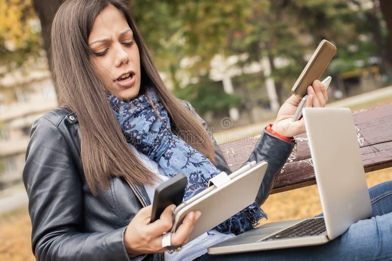 有许多屏幕、mobils、片剂和lapto的歇斯底里的女孩 免版税库存图片