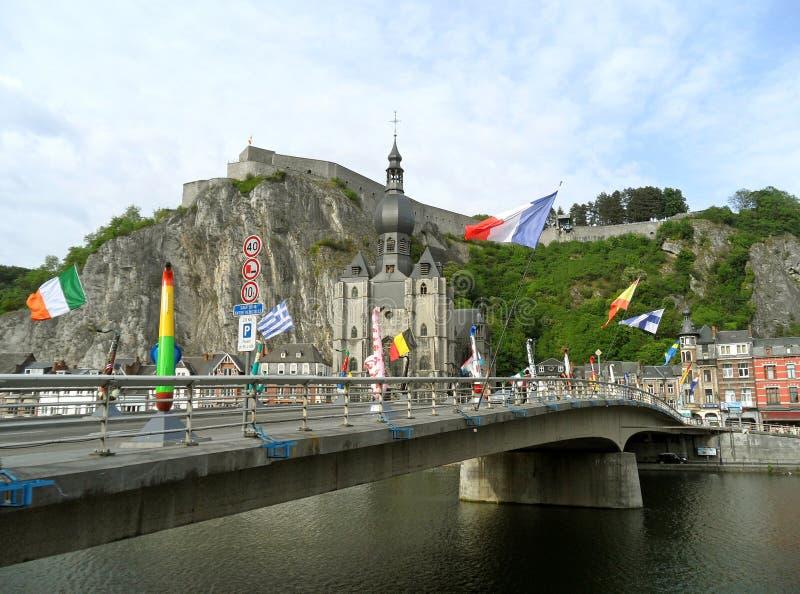 有许多巨型萨克斯管雕塑的戴高乐桥梁和Notre Dame牧师会主持的教堂在背景,迪南中 免版税图库摄影