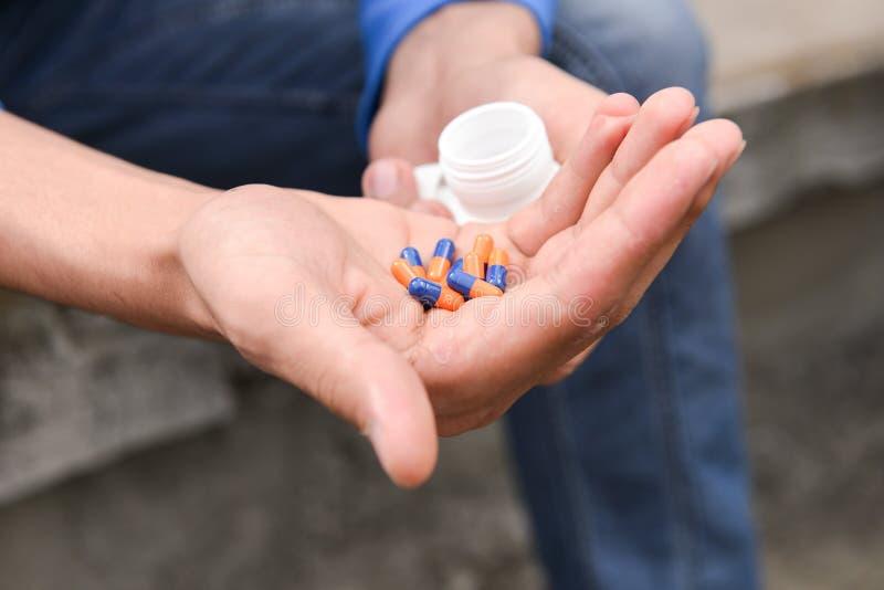 有许多片剂的沮丧的十几岁的男孩在手中 免版税库存图片