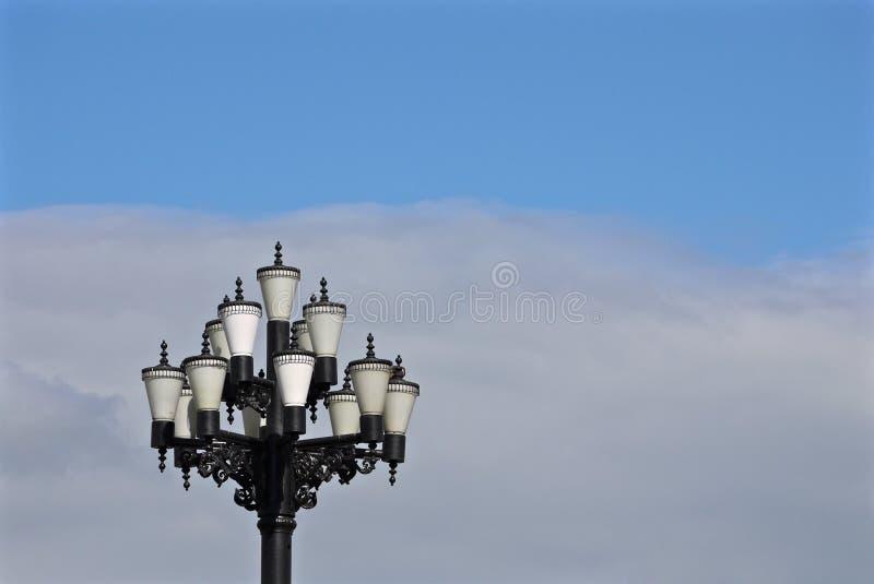 有许多玻璃盖的俏丽的街灯在天空蔚蓝背景  库存图片
