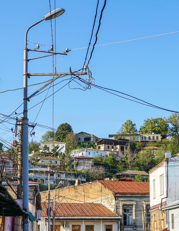 有许多电供应导线或缆绳的老点燃的岗位电话通信的 库存照片
