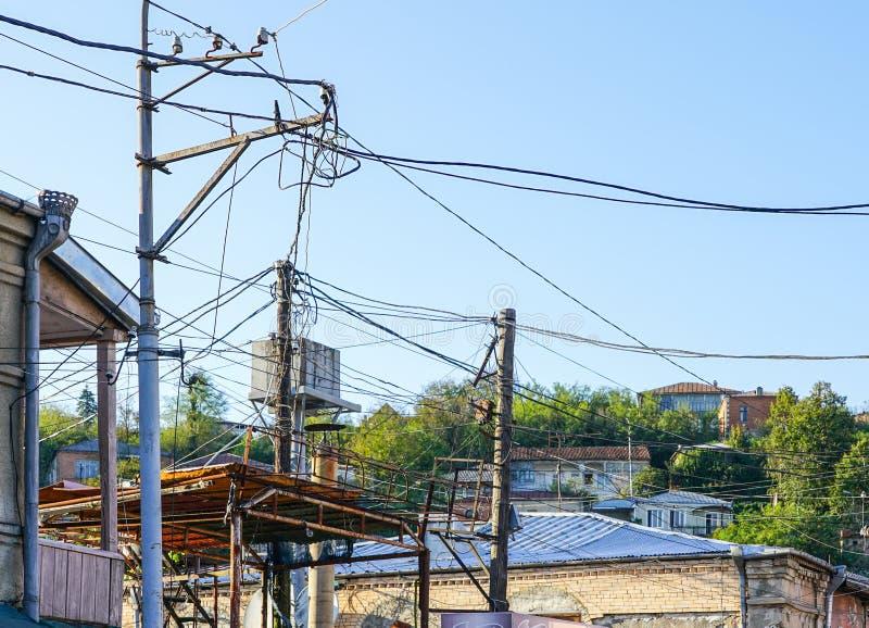 有许多电供应导线或缆绳的老点燃的岗位电话通信的 免版税库存照片