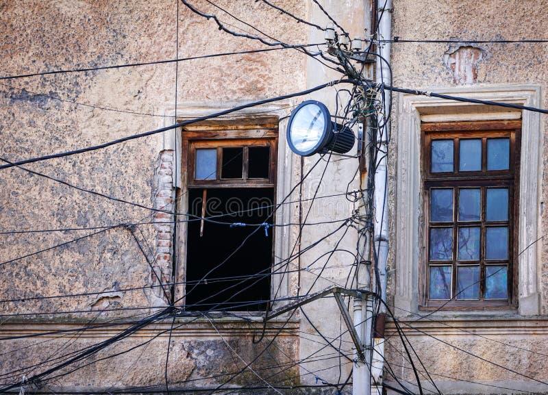 有许多电供应导线或缆绳的老点燃的岗位 库存照片