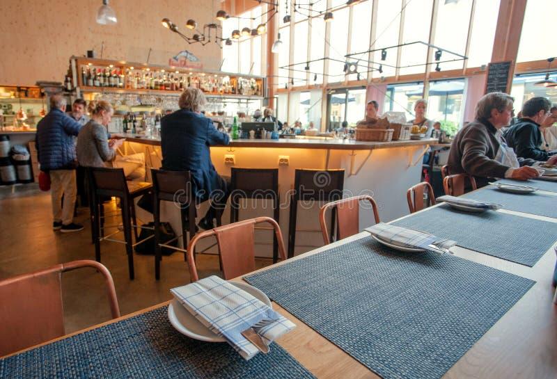 有许多的人民在现代咖啡馆或餐馆里面的工作午餐 免版税库存照片