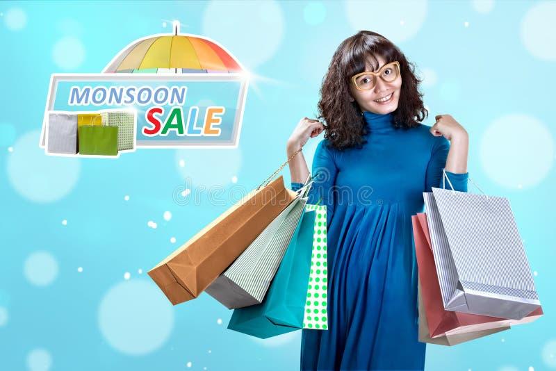 有许多的愉快的亚裔妇女在季风销售的购物袋 库存照片