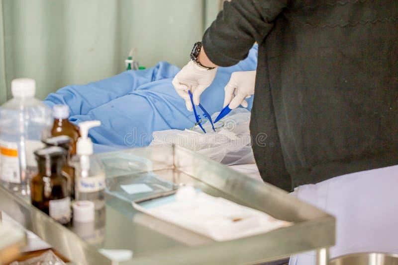 有许多的护士医学是准备或清洗她的妇女患者针在耐心部门的手术以后 图库摄影