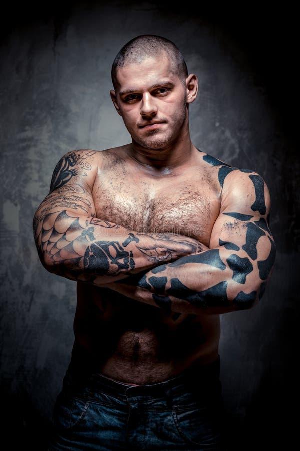 有许多纹身花刺的肌肉年轻人 库存图片