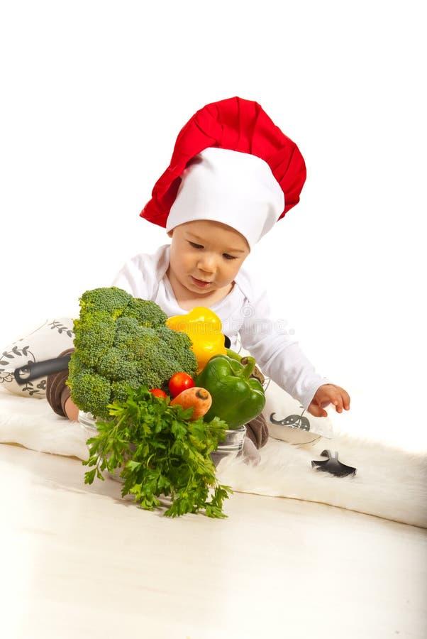 有许多菜的厨师婴孩 免版税图库摄影