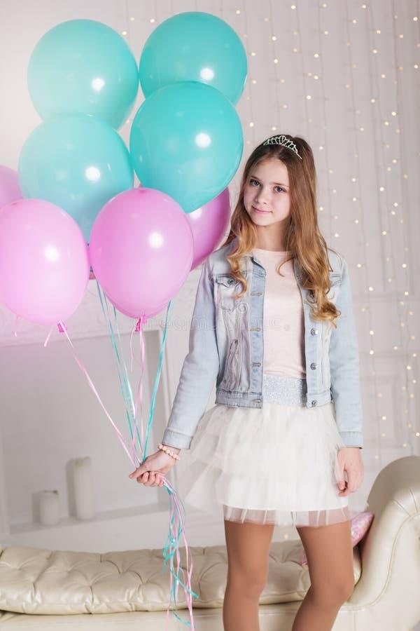 有许多蓝色和桃红色气球的俏丽的少年女孩 库存图片