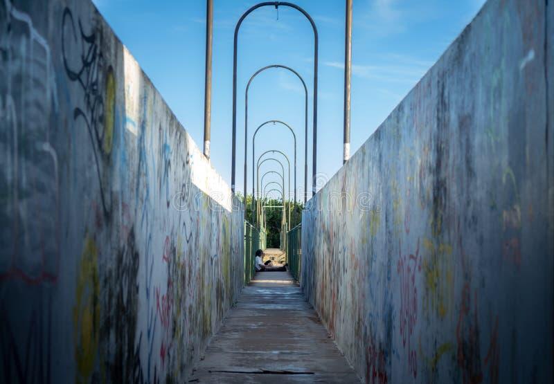 有许多街道画的狭窄的走道 坐在大厅里的人 免版税库存图片
