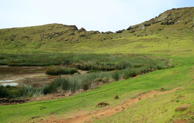 有许多被放弃的Moai雕象的火山口湖在相反倾斜,Rano Raraku火山,复活节岛,智利 免版税库存图片