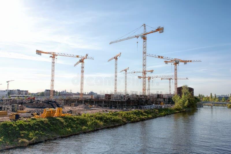 有许多起重机的大建造场所在一条河,在一晴朗,朦胧的天-柏林2018年 图库摄影