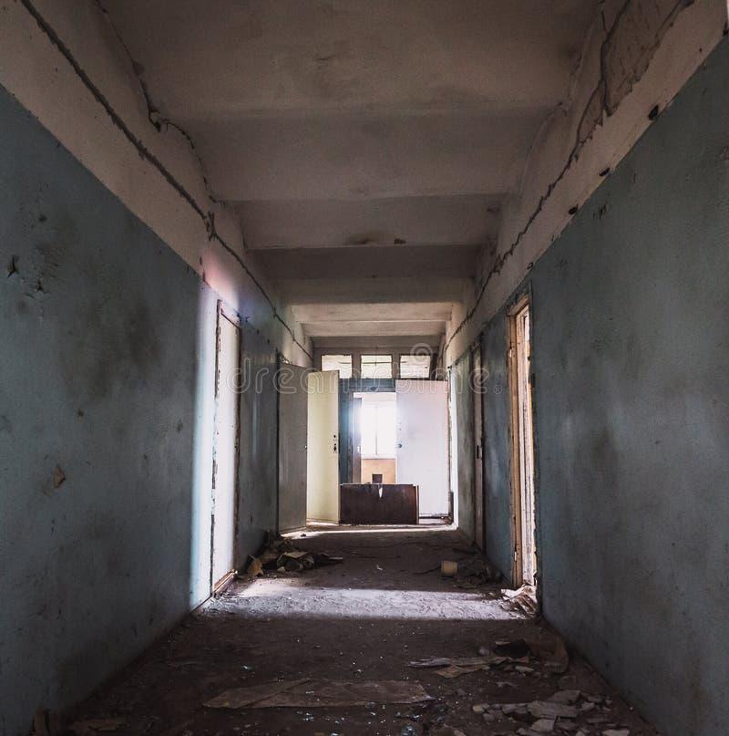 有许多门的黑暗的蠕动的走廊在被放弃的被破坏的医院、恐怖走廊或者隧道 免版税库存照片