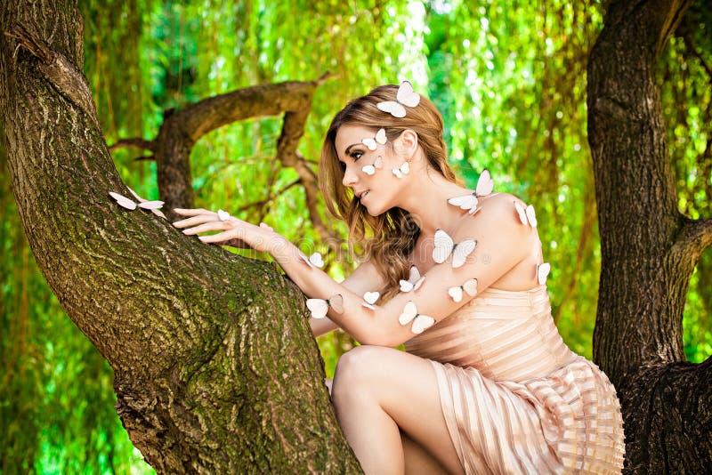 有许多蝴蝶的美丽的女孩在树 免版税库存照片