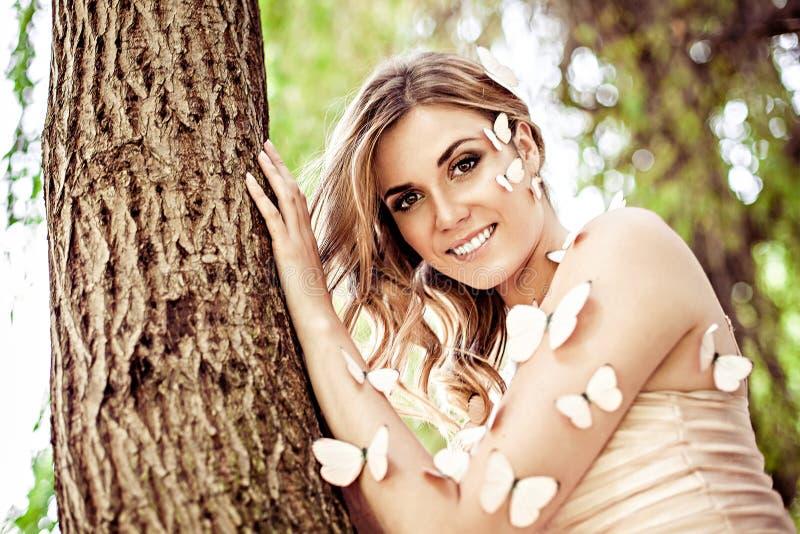 有许多蝴蝶的美丽的微笑的女性 免版税库存图片