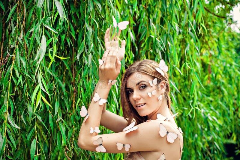 有许多蝴蝶的美丽的白肤金发的女性 图库摄影