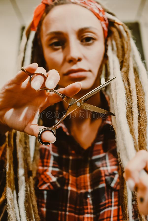 有设法的dreadlocks的女孩美发师切除您的头发 图库摄影