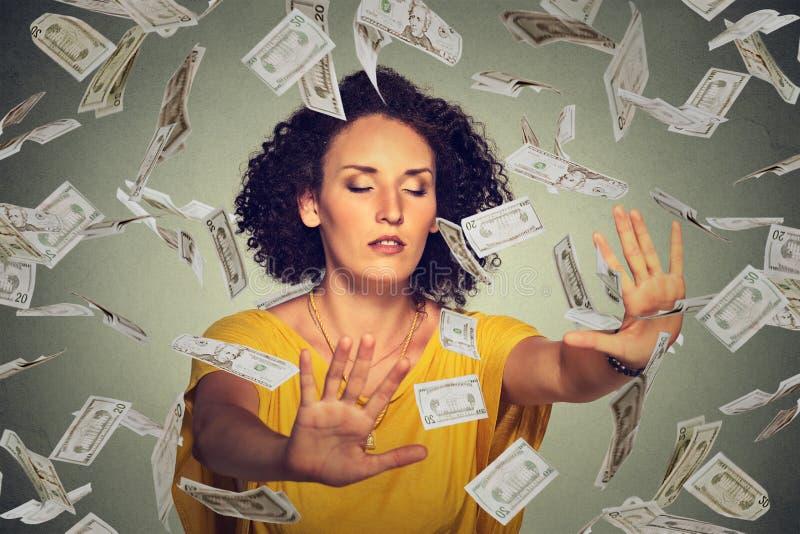 有设法闭合的眼睛的蒙住眼睛的妇女捉住飞行在空气的美元钞票 图库摄影
