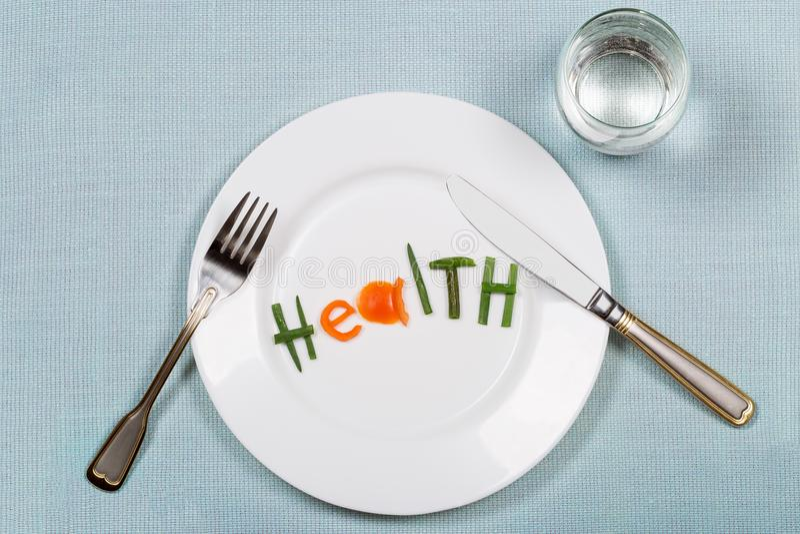 有词健康的白色板材由菜和玻璃做成五颜六色的片断纯净在蓝色teblecloth背景 免版税库存图片