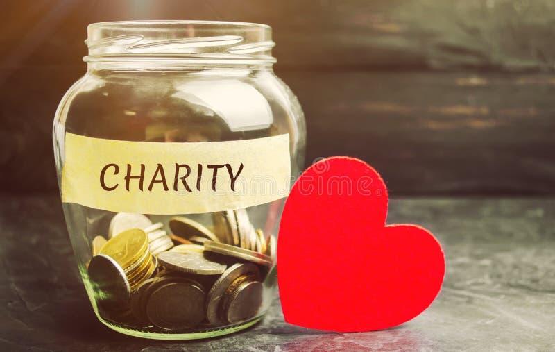 有词慈善和心脏的玻璃瓶子 积累捐赠的金钱的概念 节省额 社会医疗帮助从 库存图片