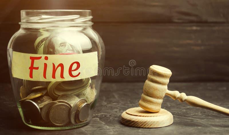 有词罚款和法官的锤子的玻璃瓶子 惩罚作为对罪行和进攻的一项处罚 财政处罚 免版税库存图片
