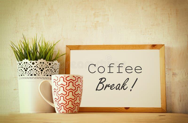 有词组咖啡休息的白色绘图板在与coffe杯子和花盆装饰的木桌 被过滤的图象 免版税图库摄影