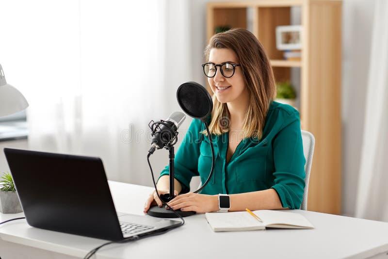 有话筒录音播客的妇女在演播室 免版税库存图片