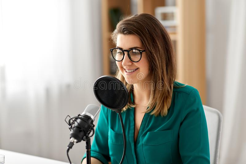 有话筒录音播客的妇女在演播室 库存图片