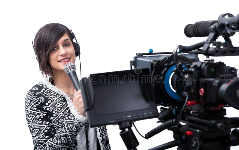 有话筒的俏丽的年轻女人在白色的新闻工作者和照相机 免版税库存图片